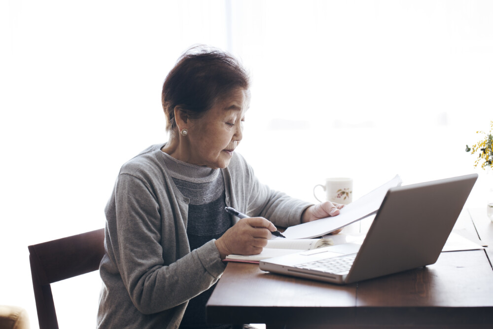 Senior woman writting a document and working at home